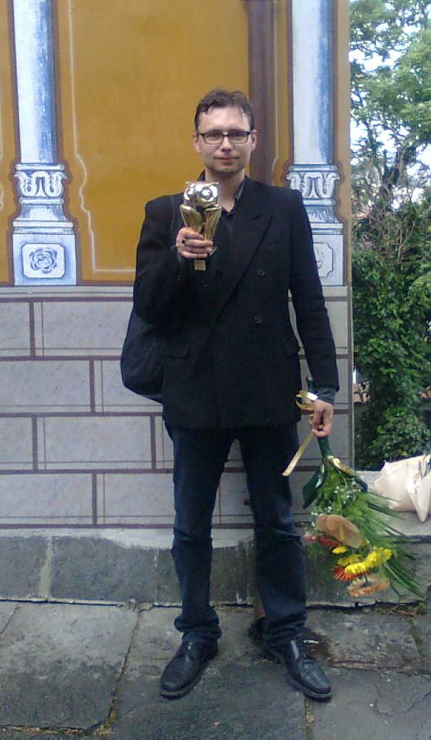 Редакторът на ``Литературен клуб`` Емилиян Николов със статуетката пред къщата-музей на ``Христо Г. Данов`` Снимка: Калоян Игнатовски